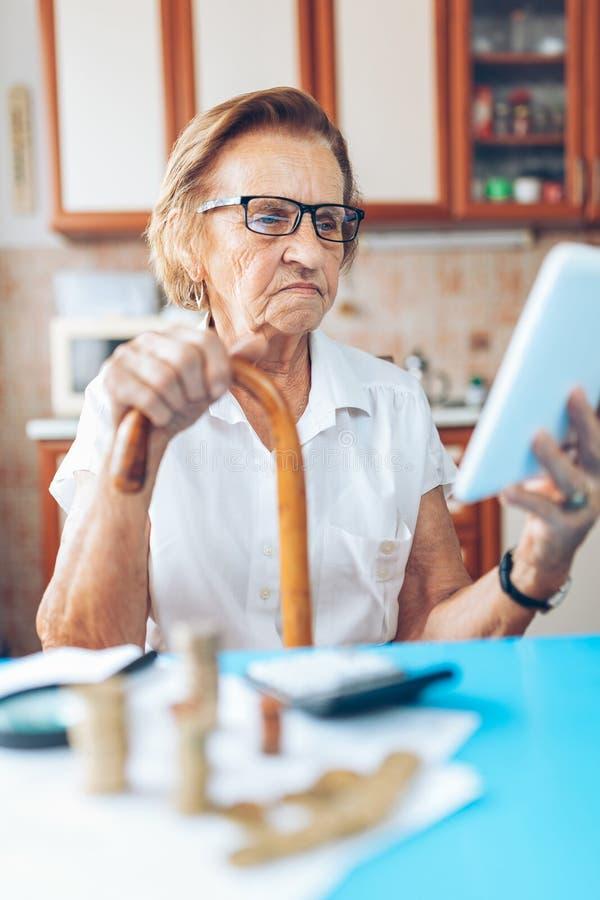 Hög kvinna som kontrollerar henne finanser och invenstments arkivfoto