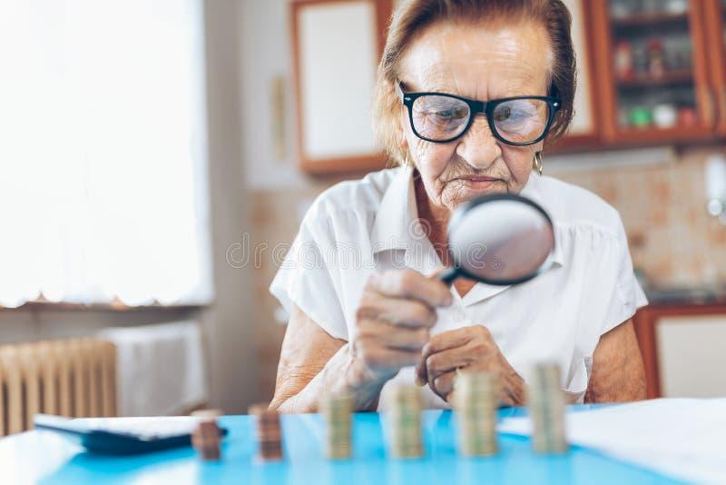 Hög kvinna som kontrollerar henne finanser och invenstments arkivfoton