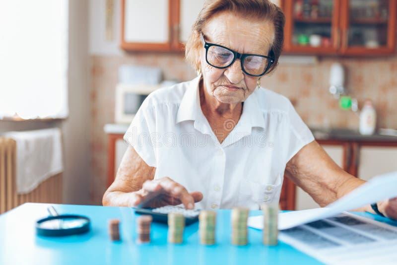 Hög kvinna som kontrollerar henne finanser och invenstments royaltyfri fotografi