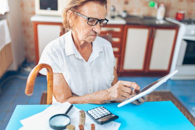 Hög kvinna som kontrollerar henne finanser och investeringar arkivbild