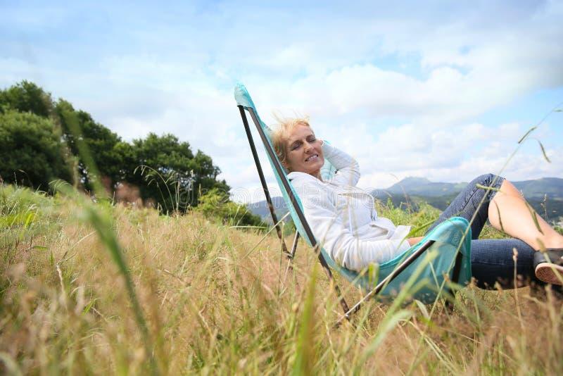 Hög kvinna som kopplar av i härligt landskap royaltyfri fotografi