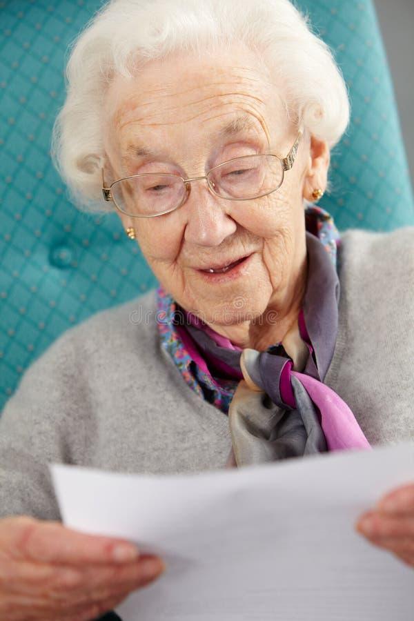 Hög kvinna som kopplar av i stolsavläsningsbokstav arkivfoton