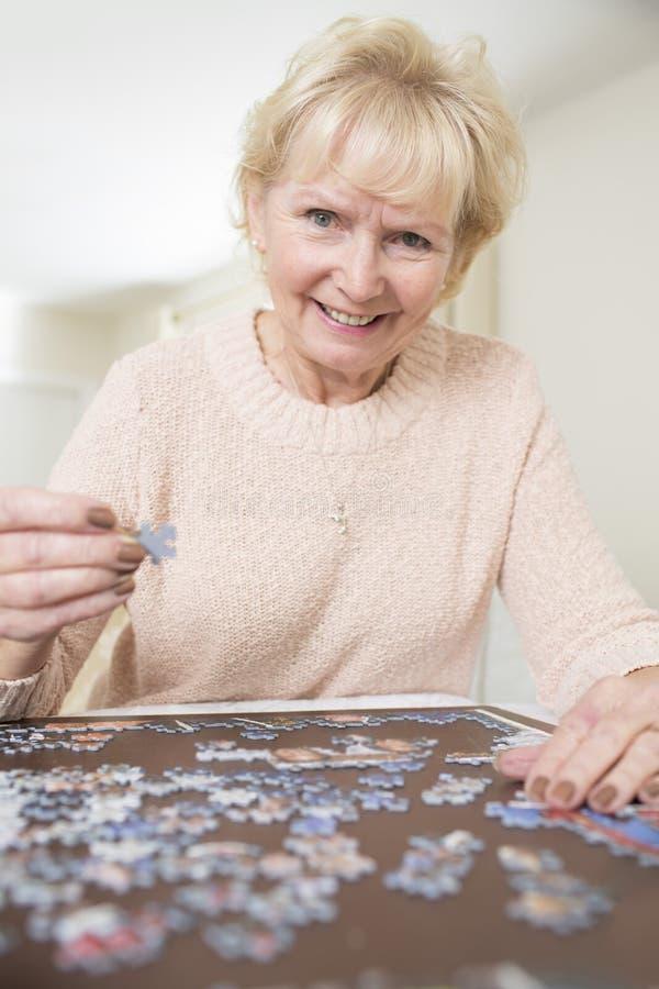 Hög kvinna som kopplar av med det hemmastadda pusslet royaltyfri foto