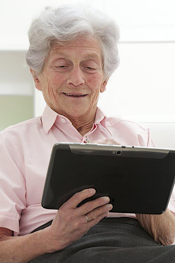 Hög kvinna som kopplar av med hennes bärbar dator arkivbilder