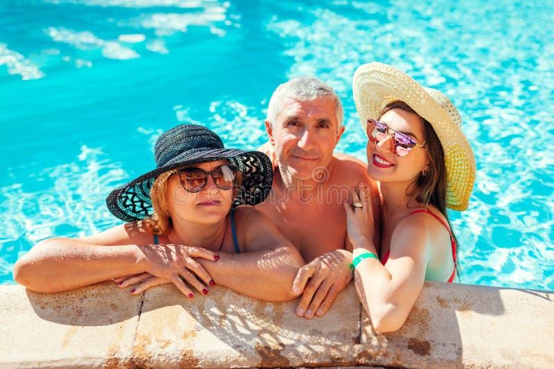 Hög kvinna som kopplar av med hennes vuxna dotter i hotellsimbassäng Folk som tycker om semester dagmamma s fotografering för bildbyråer
