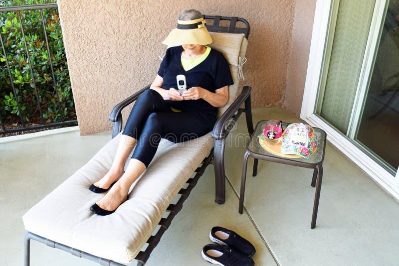 Hög kvinna som kopplar av och smsar i hennes uteplats i Laguna trän Kalifornien royaltyfri foto