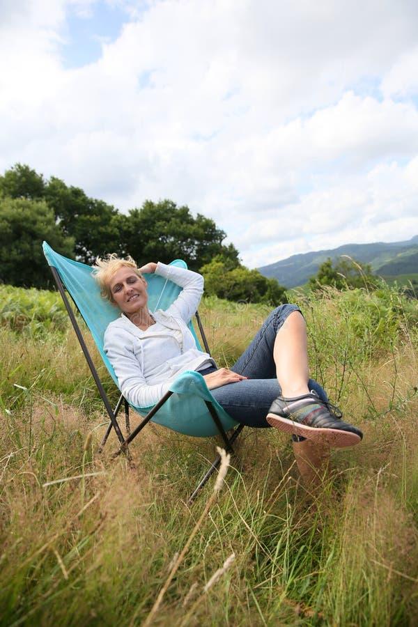 Hög kvinna som kopplar av på campa stol arkivfoton