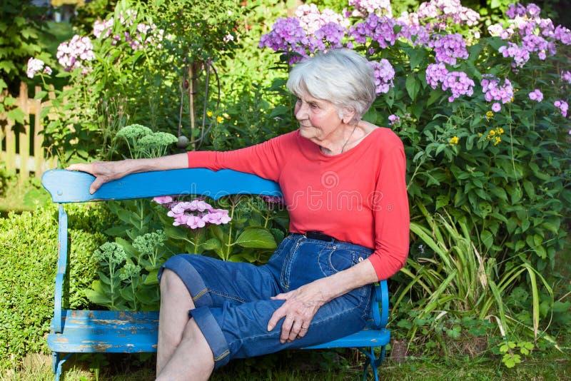 Hög kvinna som kopplar av på den trädgårds- bänken royaltyfri bild
