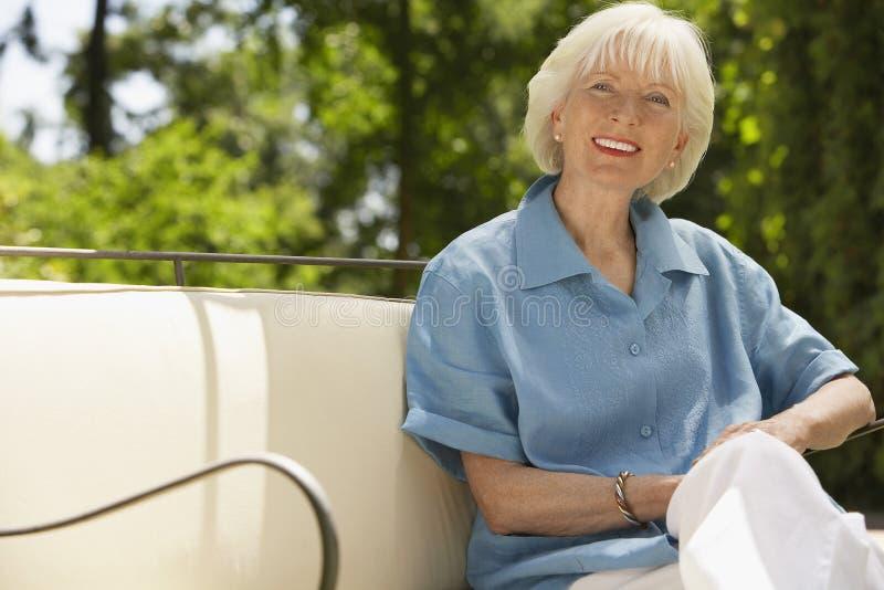 Hög kvinna som kopplar av på Sofa In Backyard royaltyfri fotografi