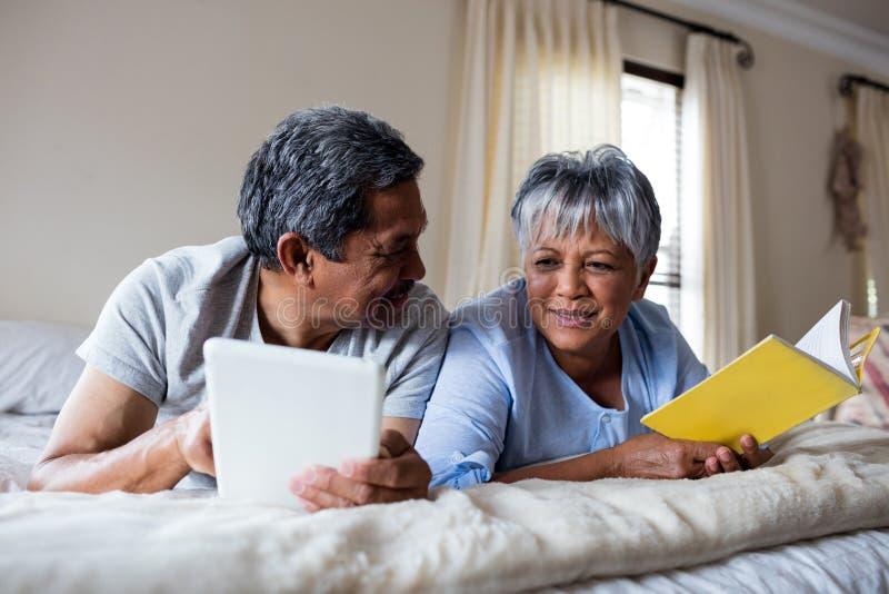 Hög kvinna som läser en bok och en hög man som använder den digitala minnestavlan på säng royaltyfria foton