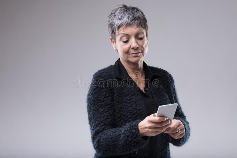 Hög kvinna som läser ett textmeddelande på en mobil royaltyfri bild