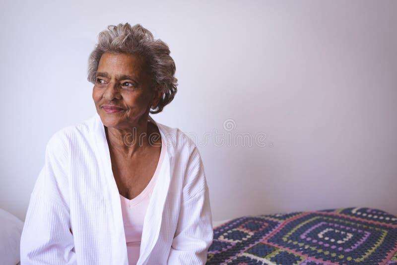 Hög kvinna som ler, medan se utanför fönstret arkivfoto