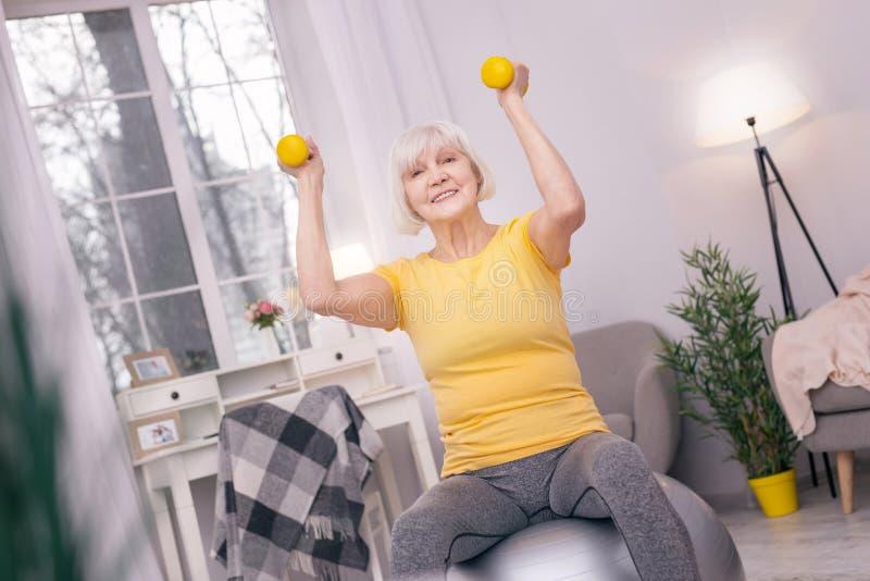 Hög kvinna som ler och övar med hantlar på yogaboll royaltyfri bild