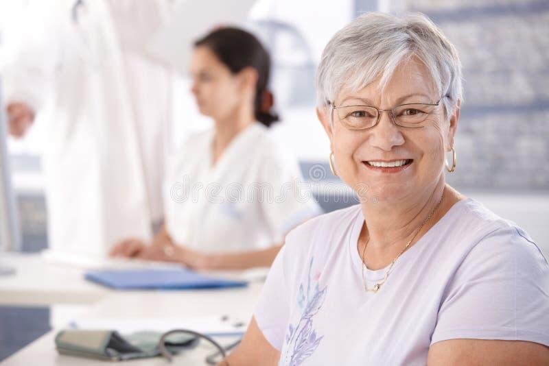 Hög kvinna som ler på doktors lokal royaltyfri bild