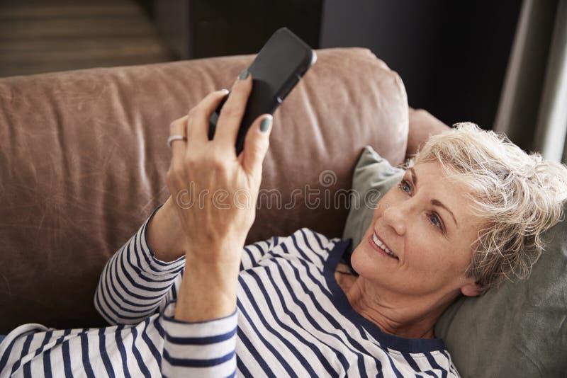 Hög kvinna som ligger på soffan genom att använda upp telefonen, högstämt slut arkivbilder
