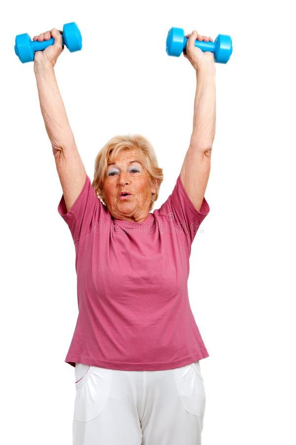 Hög kvinna som lyfter armar med vikter. arkivfoton