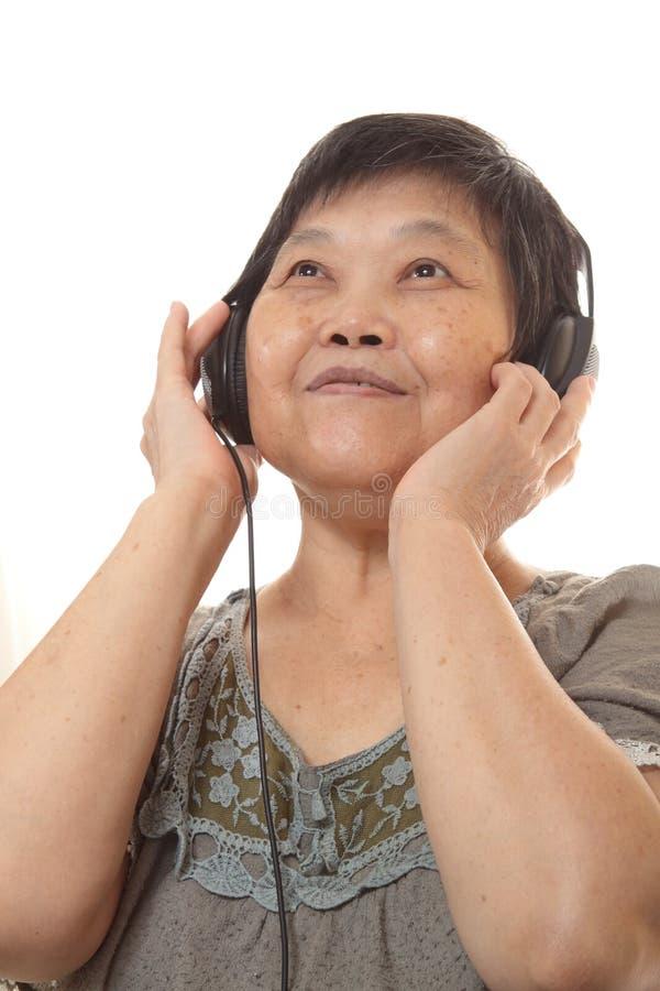 Hög kvinna som lyssnar till musik med hörlurar arkivfoton