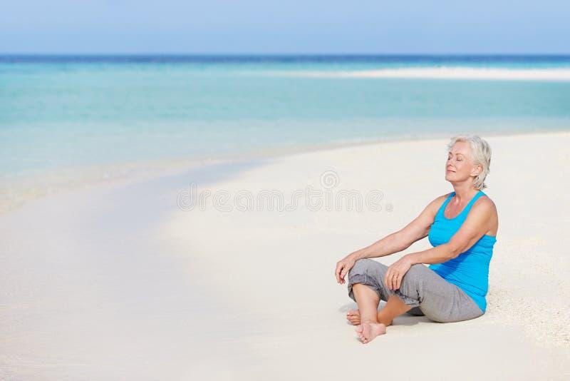 Hög kvinna som mediterar på härlig strand fotografering för bildbyråer