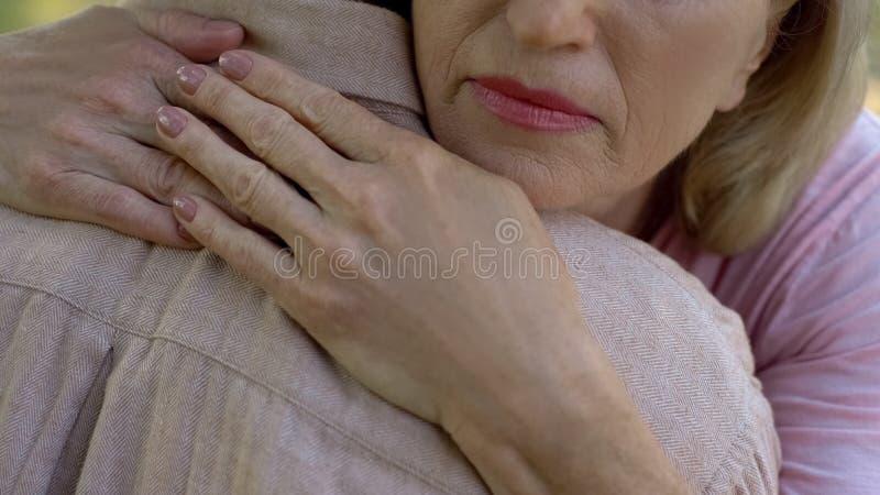 Hög kvinna som omfamnar mannen efter dåliga nyheter om sjukdomen eller förlust, familjservice arkivbild