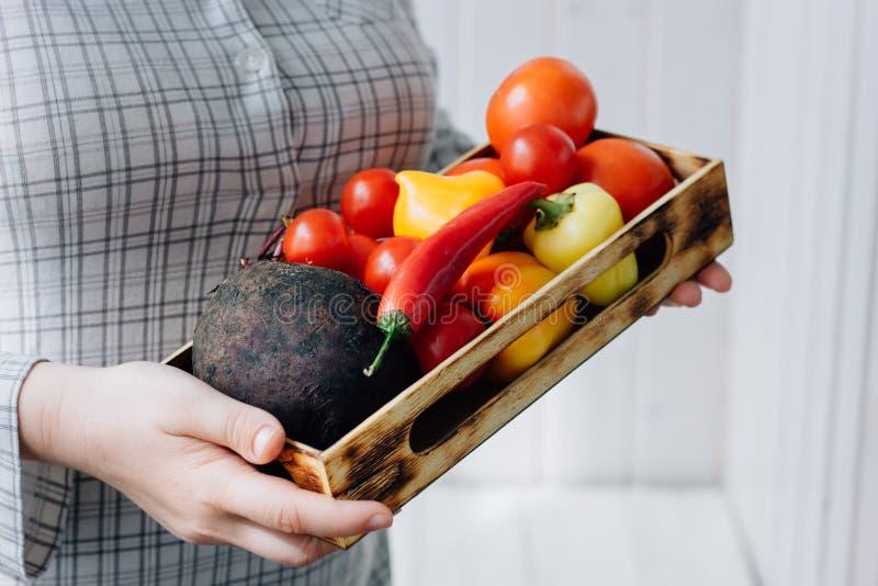 Hög kvinna som rymmer en ask med grönsaker i händer royaltyfri foto
