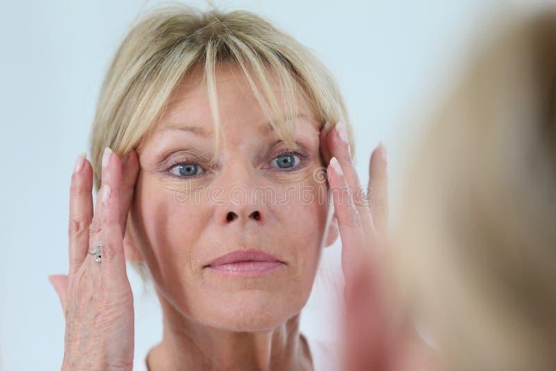Hög kvinna som ser hennes hud i spegeln royaltyfria bilder