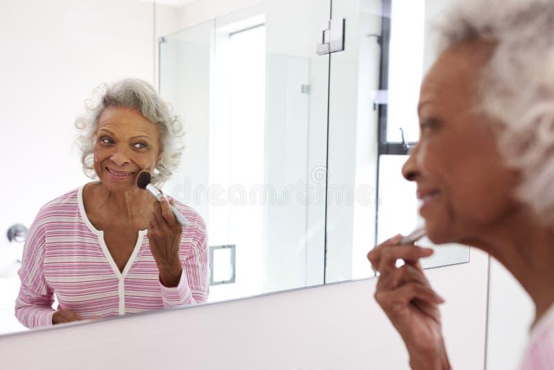 Hög kvinna som ser reflexion i badrumspegeln som sätter på smink royaltyfria bilder