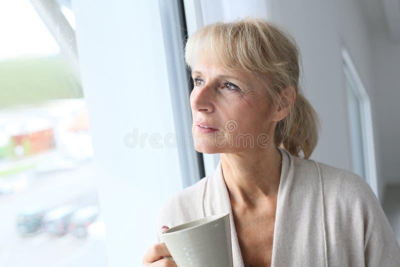 Hög kvinna som ser trhough fönstret arkivfoton