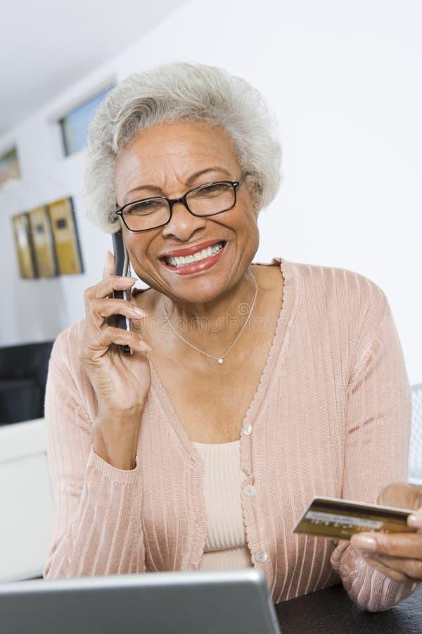 Hög kvinna som shoppar direktanslutet genom att använda mobiltelefonen och kreditkorten royaltyfria bilder