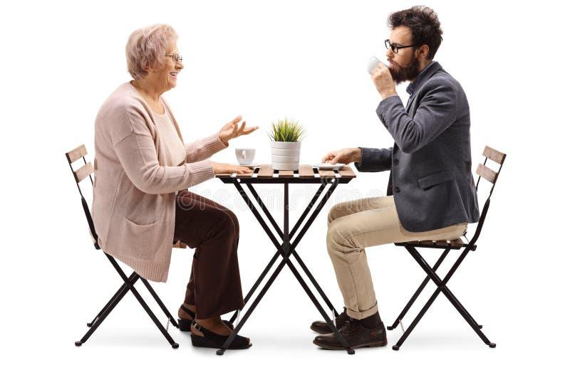 Hög kvinna som sitter på en tabell med kaffe och talar till en ung skäggig man arkivfoton