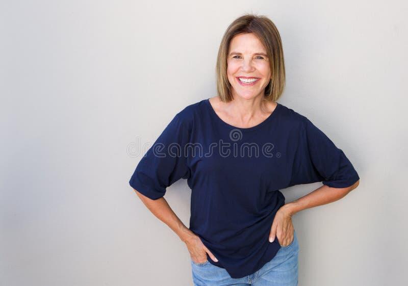 Hög kvinna som skrattar mot den gråa väggen royaltyfria foton