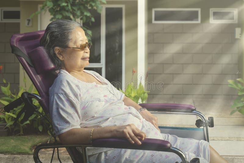 Hög kvinna som solbadar i morgonen royaltyfri bild
