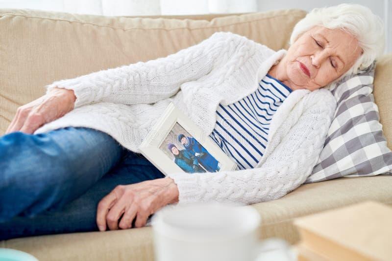 Hög kvinna som sovande faller med fotoet av maken royaltyfri bild
