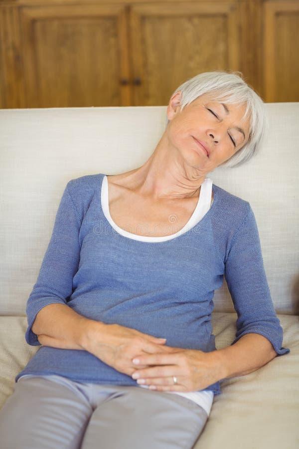 Hög kvinna som sover på soffan i vardagsrum royaltyfri foto