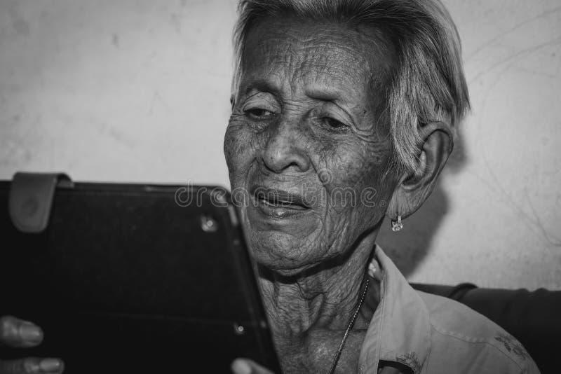 Hög kvinna som spelar minnestavlan fotografering för bildbyråer