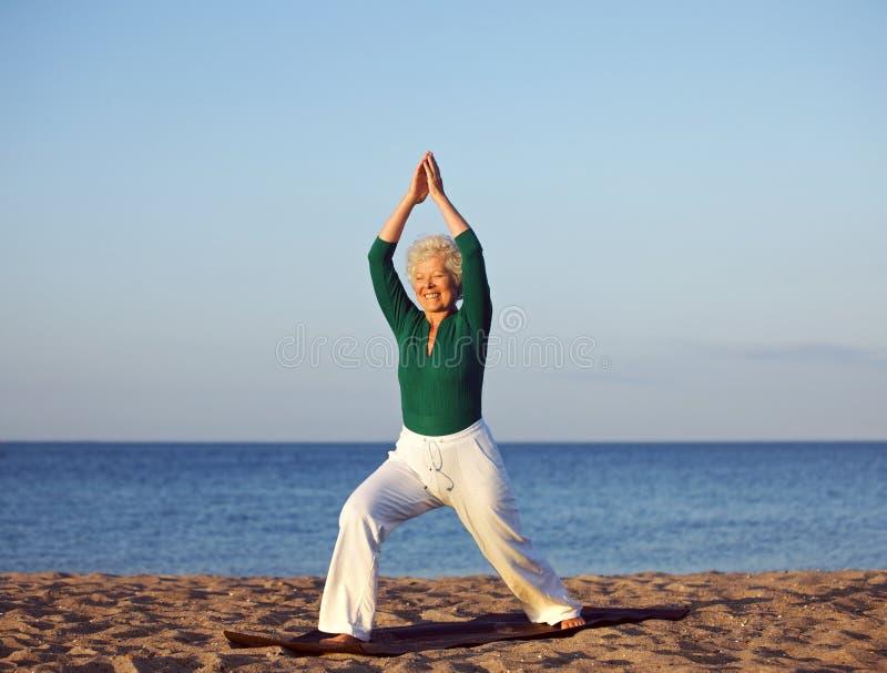Hög kvinna som sträcker mot strandbakgrund royaltyfri foto