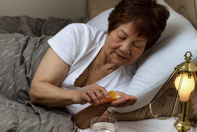 Hög kvinna som tack vare tar henne medicin på sjukdomen för nattetid royaltyfri fotografi