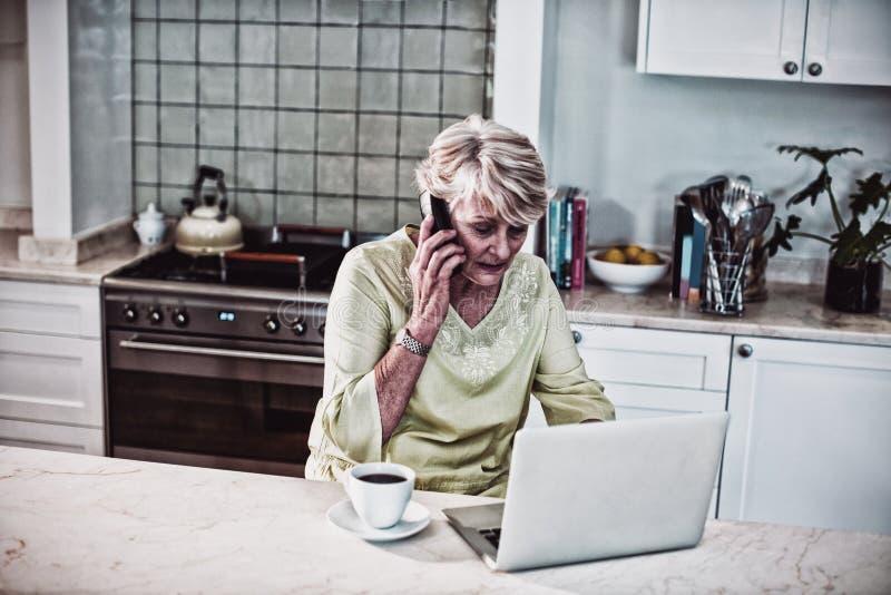 Hög kvinna som talar på mobiltelefonen, medan genom att använda bärbara datorn fotografering för bildbyråer