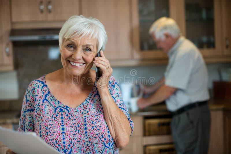 Hög kvinna som talar på mobiltelefonen medan man som arbetar i kök arkivfoton