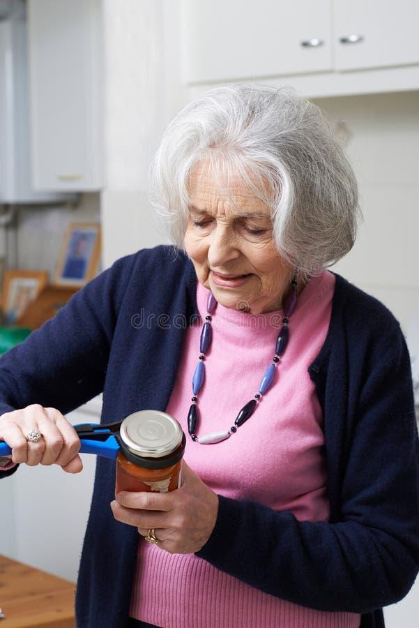 Hög kvinna som tar locket av kruset med kökhjälpmedlet royaltyfria foton