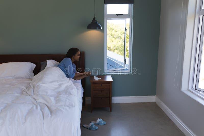 Hög kvinna som tar medicin med exponeringsglas av vatten, medan ligga i säng hemma arkivbild