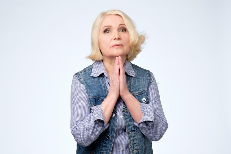 Hög kvinna som tigger och ber samman med hopputtryck på framsida arkivfoto