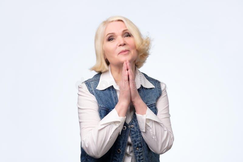 Hög kvinna som tigger och ber samman med hopputtryck på framsida royaltyfria foton