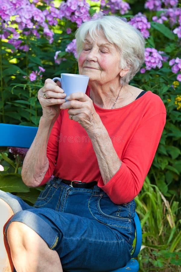 Hög kvinna som tycker om aromen av hennes kaffe arkivbild