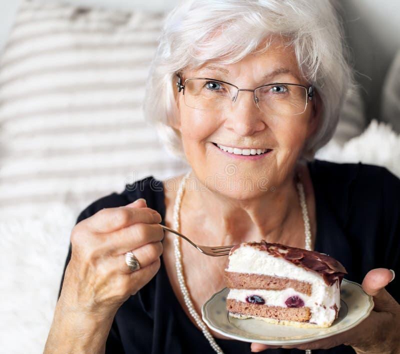 Hög kvinna som tycker om kakan royaltyfria bilder