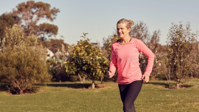 Hög kvinna som utomhus ler och joggar på en solig morgon royaltyfria bilder