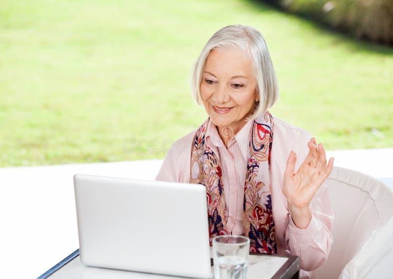 Hög kvinna som vinkar medan videoConferencing på arkivfoton