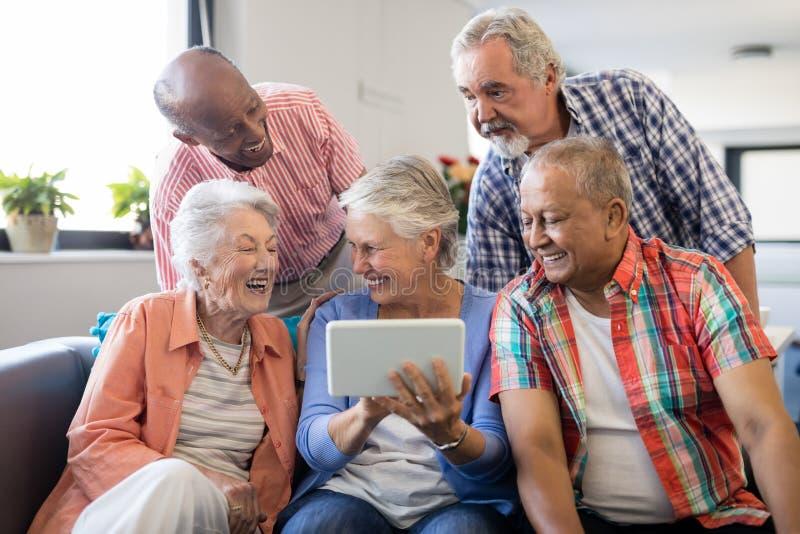 Hög kvinna som visar den digitala minnestavlan till gladlynta vänner arkivfoton