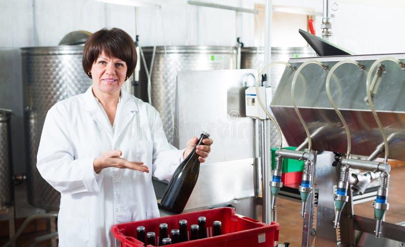 Hög kvinnaarbetare som buteljerar mousserande vin arkivfoto