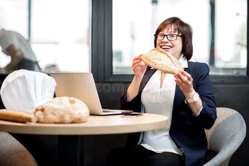 Hög kvinnabagare som kontrollerar brödkvalitet arkivfoton