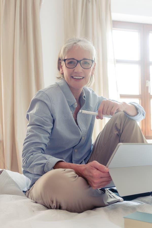 Hög kvinnafreelancer i hennes studie med datoren arkivbild
